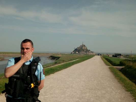 French gendarme is seen near Mont Saint-Michel as it was closed and evacuated after a man threatened he installed a bomb on the island
