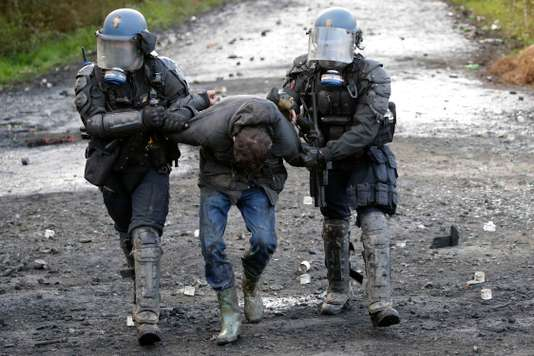 French gendarmes apprehend a protester during clashes in the zoned ZAD (Deferred Development Zone) in Notre-Dame-des-Landes
