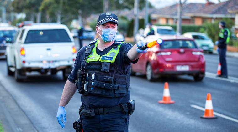 Police stop drivers at a checkpoint as coronavirus disease cases spike in Melbourne