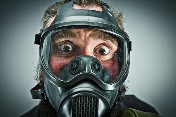 Scared male prepper wearing gas mask